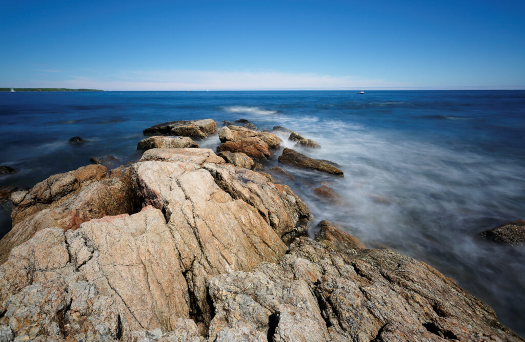 Rocks and slow motion ocean wave at Rye Harbor State Park, Portsmouth NH, USA. The park affords scenic views of the Atlantic Ocean, the Isles of Shoals, and Rye Harbor, also called Ragged Neck.
